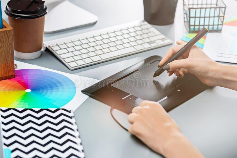 Het grijze bureau met laptop, blocnote met leeg blad, pot van bloem, naald en tablet voor het retoucheren stock afbeeldingen