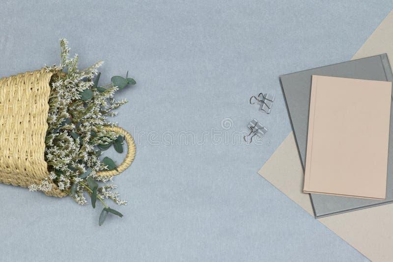 Het grijze notitieboekje & de paperclippen, de roze nota & het document, de stromand met witte bloemen en de eucalyptus vertakken stock foto