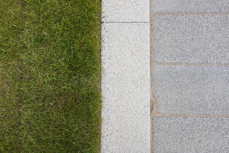Het grijze steen bedekken & rand naast groen grasgazon royalty-vrije stock afbeelding