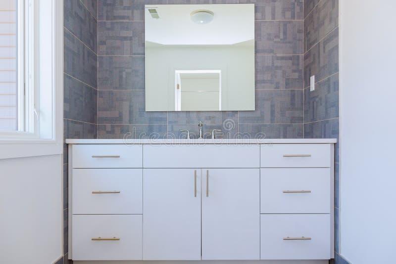 Het grijze steenpatroon betegelde eigentijdse badkamers het binnenlandse ontwerp met minimale natuurlijke houten meubilairdetails stock afbeelding