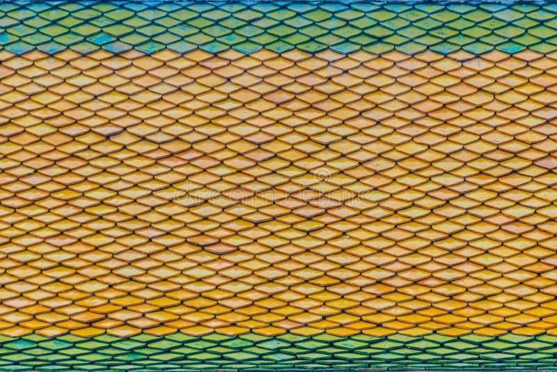 Het groen-oranje dak betegelt patroon op dak van Thaise Boeddhistische chur stock fotografie