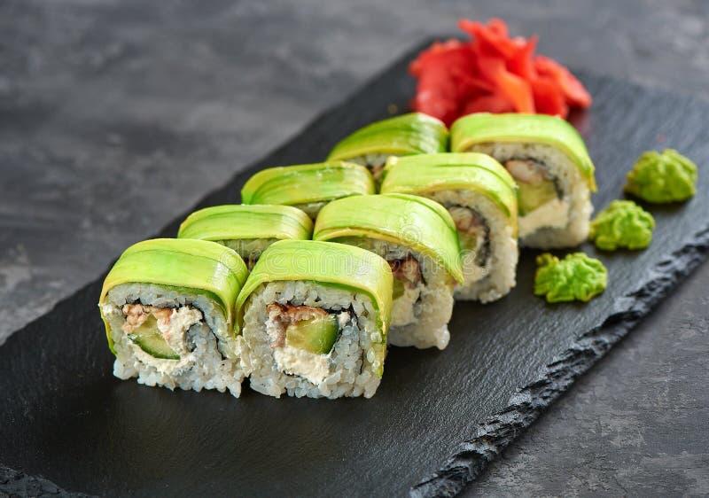 Het groene broodje van draaksushi met paling en avocado stock afbeeldingen