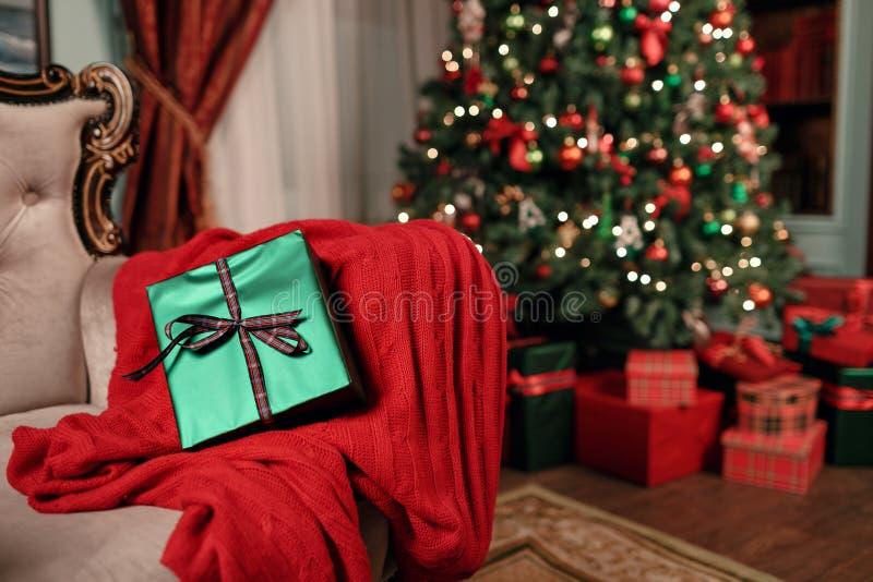 Het groene close-up van de Kerstmisgift op voorgrond Boog van rood lint Abstracte achtergrond met vage lichten en boom exemplaar royalty-vrije stock afbeeldingen