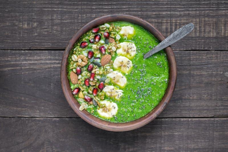 Het groene detoxontbijt smoothie werpt bedekt met granola, banaan, granaatappel, pompoen en chiazaden met een lepel stock afbeeldingen