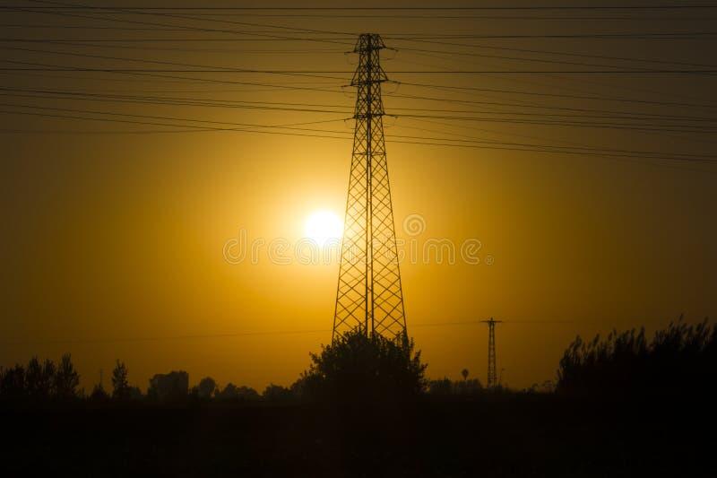 Het groene energieconcept, Elektriciteitspost, sluit omhoog de lijnen van de hoogspanningsmacht bij zonsondergang De post van de  royalty-vrije stock foto