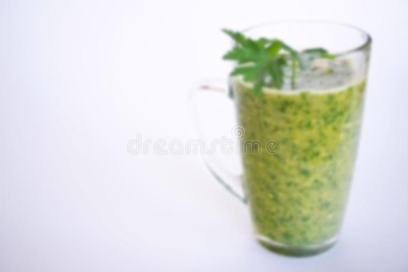 Het groene fruit en plantaardige smoothie met een twijg van peterselie in een transparant glas overvallen op een witte achtergron stock afbeeldingen
