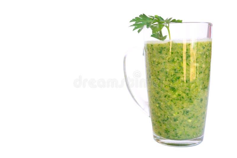 Het groene fruit en plantaardige smoothie met een twijg van peterselie in een transparant glas overvallen op een witte achtergron stock fotografie