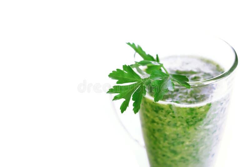 Het groene fruit en plantaardige smoothie met een twijg van peterselie in een transparant glas overvallen op een witte achtergron royalty-vrije stock afbeeldingen