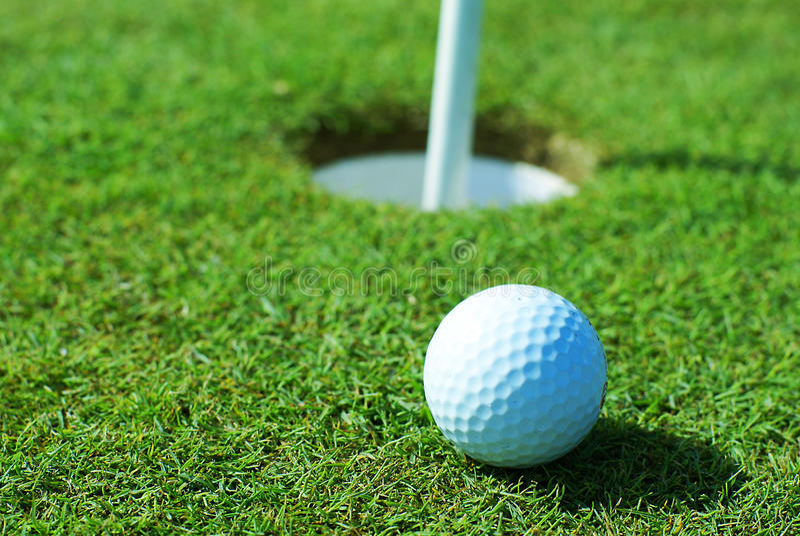 Het groene gras van de golfbal voor gat stock foto