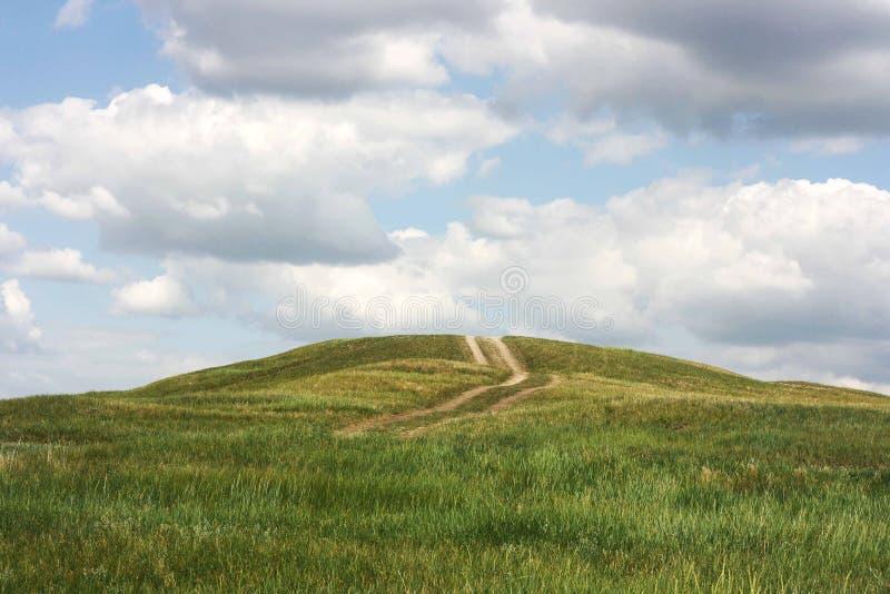 Het groene landschap van het grasgebied met weg, wolken en blauwe hemel royalty-vrije stock foto