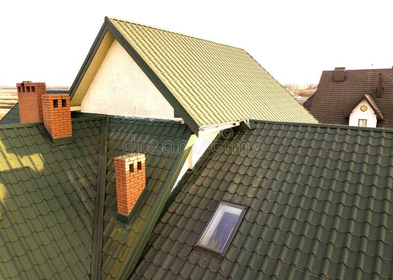 Het groene metaal shingled huisdak met zolder plastic venster en baksteenschoorsteen stock fotografie
