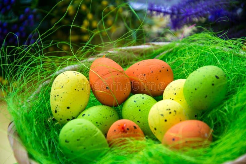 Het groene nest in een mand met kleine kleurrijke paaseieren, decoratie, het concept van close-uppasen, vakantietraditie, vertroe stock afbeelding