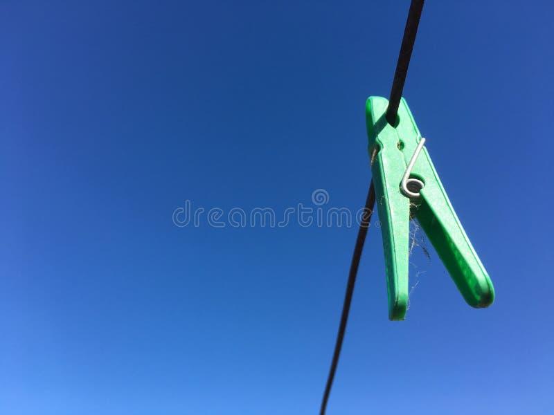 Het groene plastic wasknijperwasknijper hangen van de lijn van de draadwasserij in openlucht royalty-vrije stock foto's