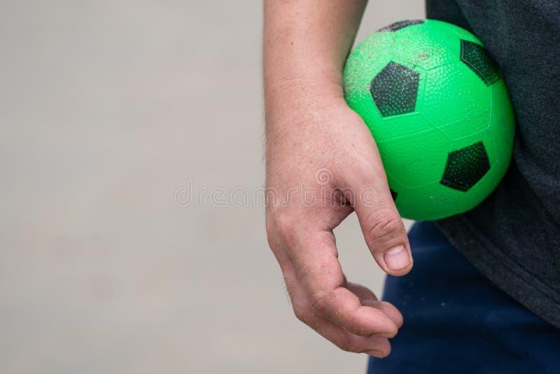 Het Groene Rubbervoetbalstuk speelgoed werd gehouden in de hand van het mannetje stock fotografie