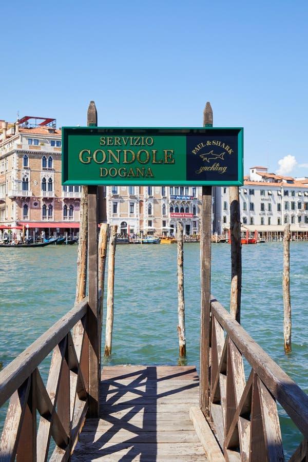 Het groene teken van de gondeldienst en houten pijler met groot kanaal in Venetië, Italië royalty-vrije stock afbeeldingen