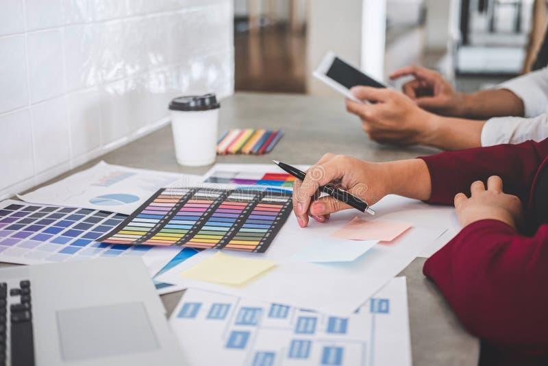 Het groepswerk van creatieve ontwerpers die aan nieuw project werken en kiest de steekproeven van het kleurenmonster voor selecti stock afbeeldingen