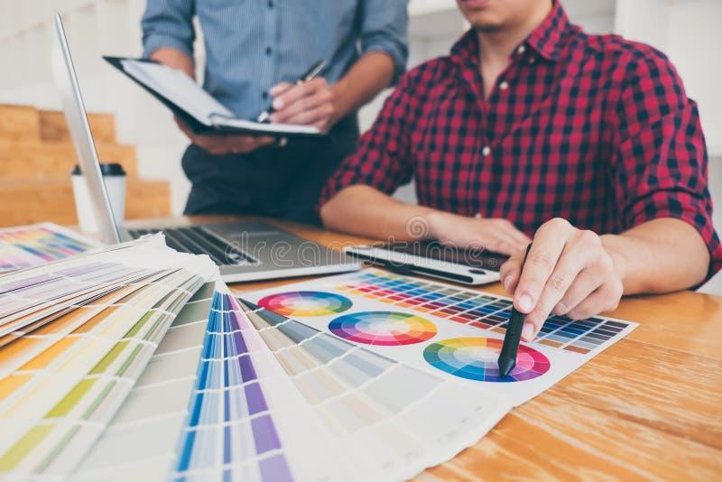 Het groepswerk van jonge creatieve ontwerpers die aan project samenwerken en kiest de steekproeven van het kleurenmonster voor se stock foto's