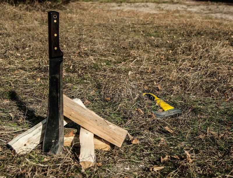 Het grote de staalmes of machete plakte in de grond, brandhout en de bijl het liggend op het gras stock afbeelding
