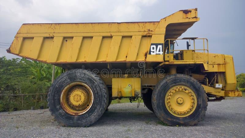 Het grote en zware Gele zijaanzicht van de stortplaatsvrachtwagen royalty-vrije stock fotografie