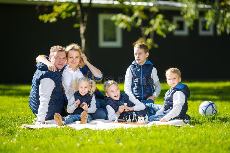 Het grote Familie Ontspannen in Groene Aard Het gelukkige familieportret op openlucht, groepeert zes mensen zit op gras, zomer royalty-vrije stock foto's