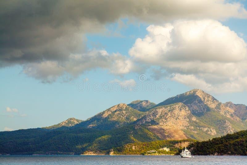 Het grote jacht drijft nabijgelegen rotsachtige kust met bomen in Aegea royalty-vrije stock foto's