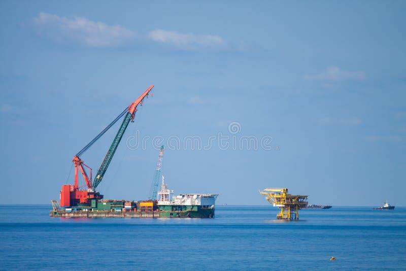 Het grote kraanschip die het platform installeren in zee, kraanaak die mariene zware liftinstallatie doen werkt stock foto