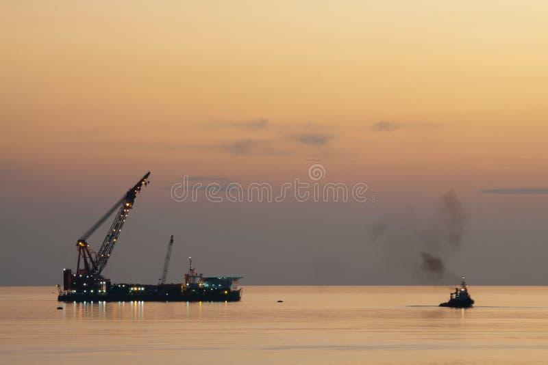 Het grote kraanschip die het platform installeren in zee, kraanaak die mariene zware liftinstallatie doen werkt royalty-vrije stock foto