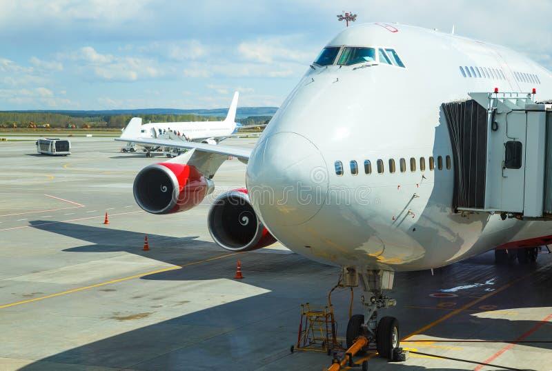 Het grote passagiersvliegtuig landt aan baan van luchthaven met passagiers die op het vliegtuig op de achtergrond komen royalty-vrije stock afbeeldingen
