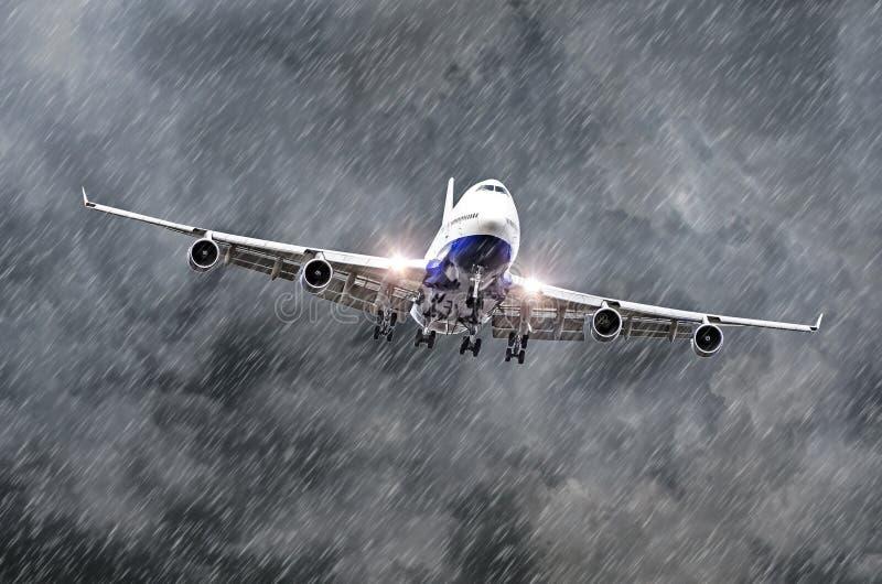 Het grote passagiersvliegtuig nadert het landen bij de luchthaven van regen, slecht weer stock foto