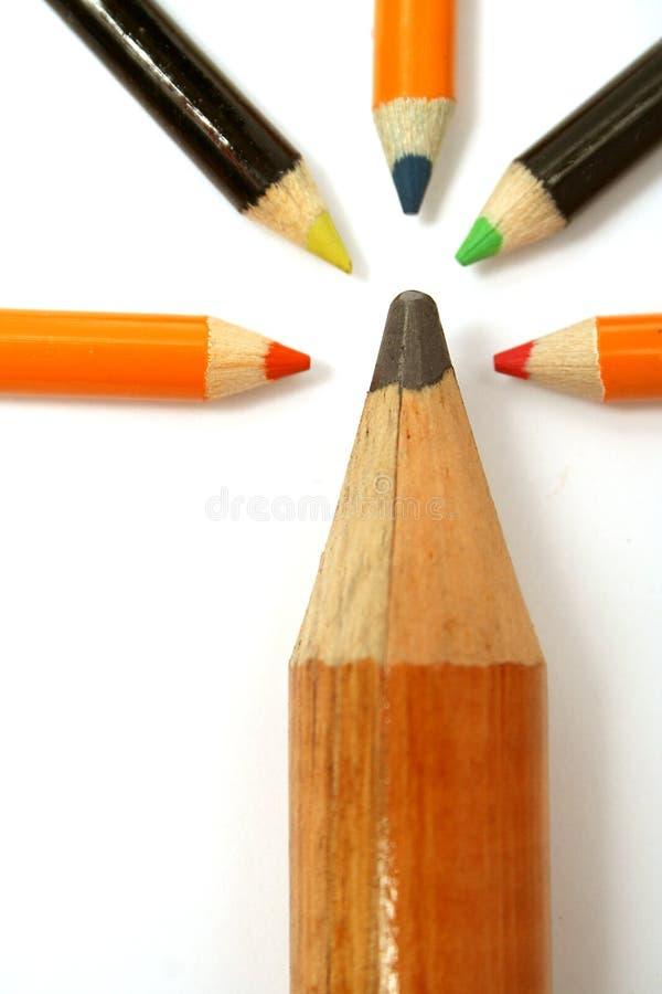 Het grote potlood en vijf kleine kleurenpotloden op een verticaal stock foto's