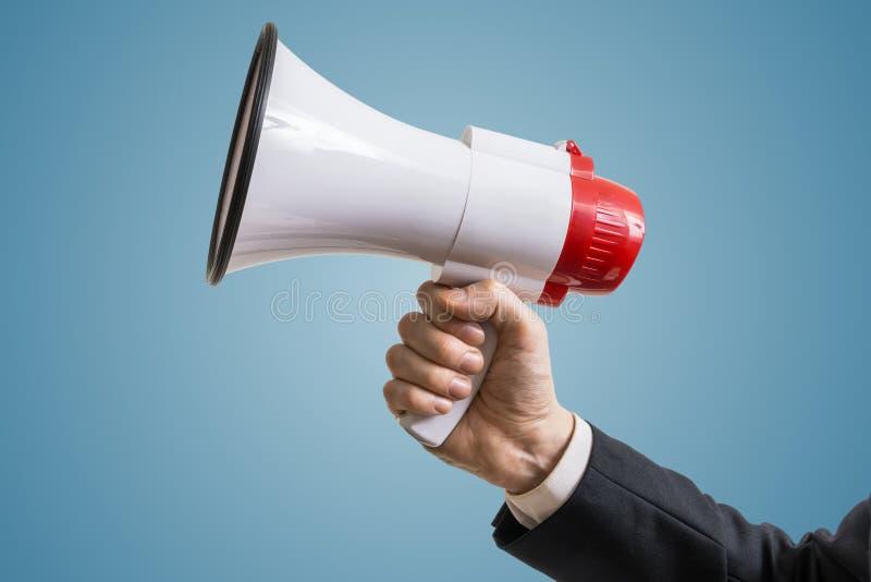 Het grote rood dobbelt met vragen De hand houdt megafoon stock fotografie
