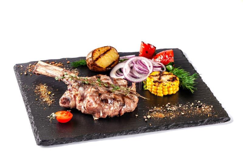 Het grote vleeslapje vlees op het geroosterde been, diende met geroosterde groenten, graan, rode ui, paprika's, aardappels Het mo stock foto