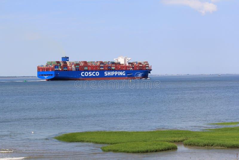 Het grote vrachtschipcosco verschepen navigeert door het overzees langs het groene zoute moeras in de zomer stock foto