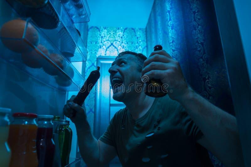 Het gulzige mens chomping op een salami tijdens de nacht royalty-vrije stock foto