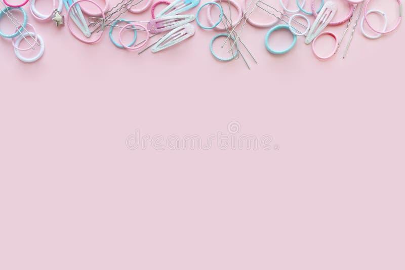 Het haar scrunchies en de haarspelden op roze achtergrond, vlak schoonheidsconcept, leggen royalty-vrije stock afbeelding
