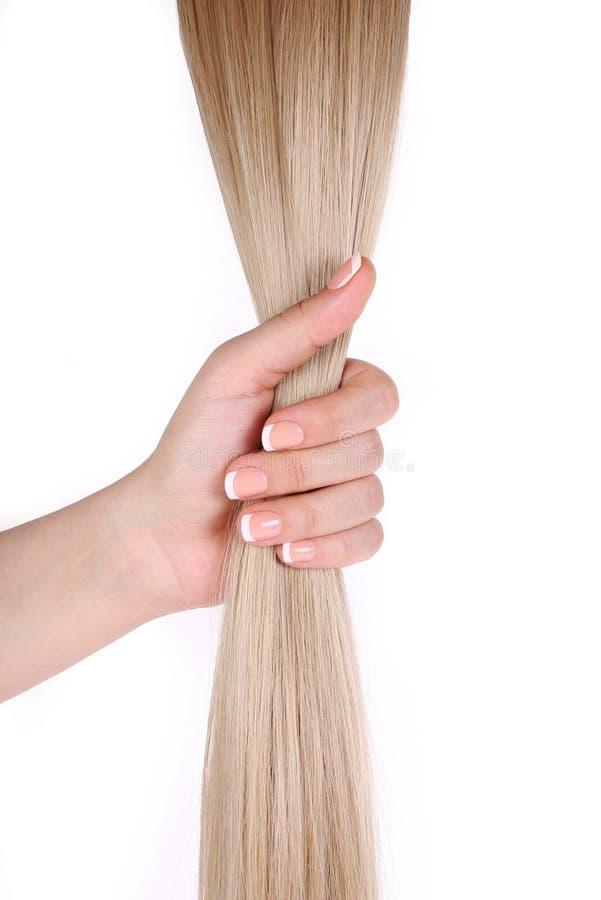 Het haar van de blonde in vrouwelijke hand die op wit wordt geïsoleerdt royalty-vrije stock foto