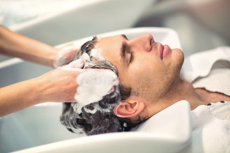Het haar van de kapperwas aan haar knappe cliënt stock afbeeldingen