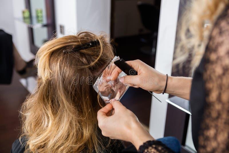 Het Haar van de Vrouwelijke Cliënt van kapperputting foils in royalty-vrije stock afbeelding