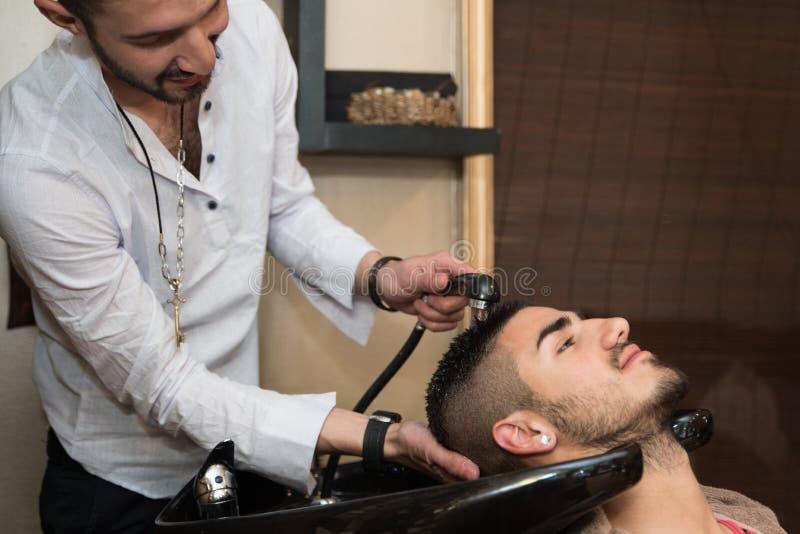 Het haar van de wasmens in de herenkapper van de schoonheidswoonkamer stock afbeeldingen