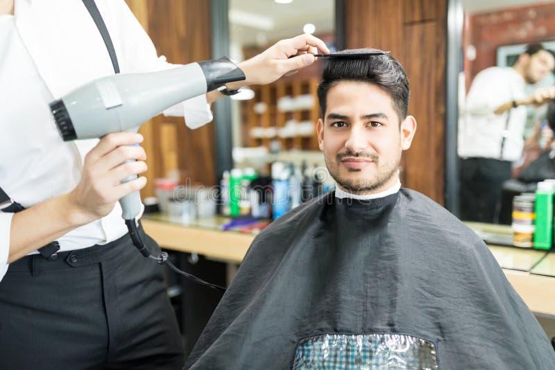Het Haar van kapperdrying customer ` s met Hairdryer in Salon royalty-vrije stock afbeelding