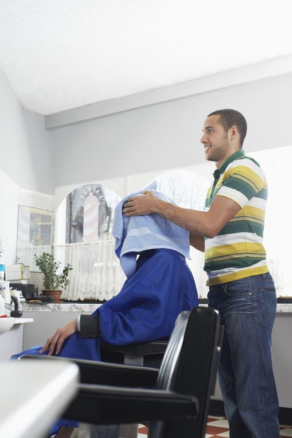 Het Haar van kapperdrying man met Handdoek royalty-vrije stock afbeeldingen