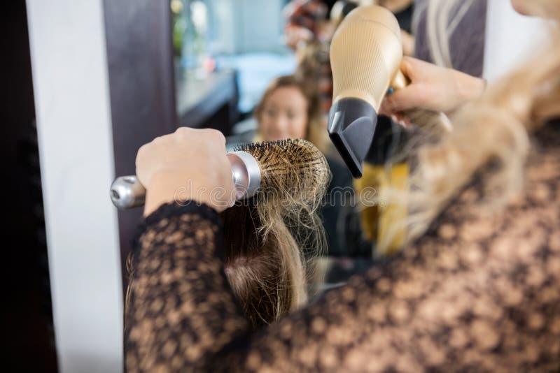 Het Haar van kapperstyling female customer in Salon royalty-vrije stock afbeelding