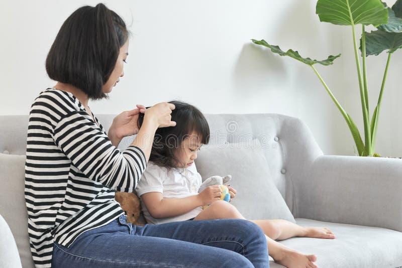 Het haar van het moedervlechten van haar dochter stock fotografie