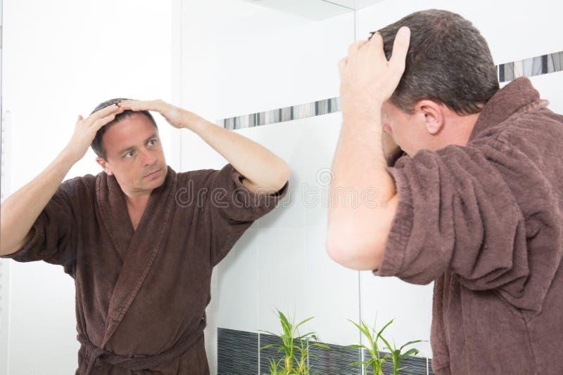 Het haarverlies van mensencontroles in de badkamers die in een spiegel kijken royalty-vrije stock afbeeldingen