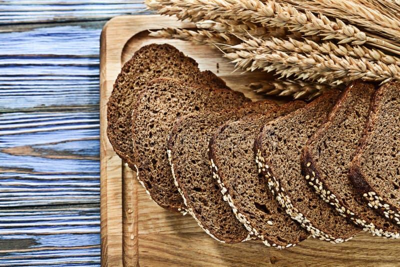 Het hakbord gesneden bruin brood van tarweoren op uitstekende houten B stock fotografie