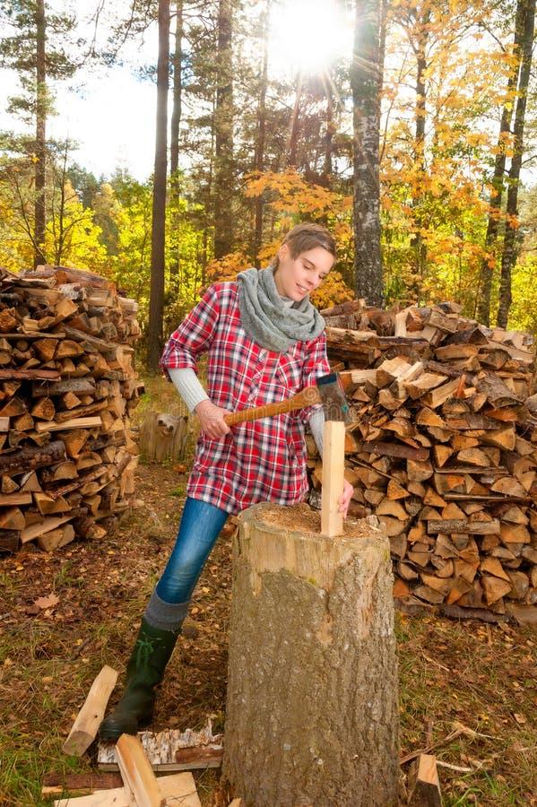 Het hakkende en verdelende hout van de vrouw stock foto