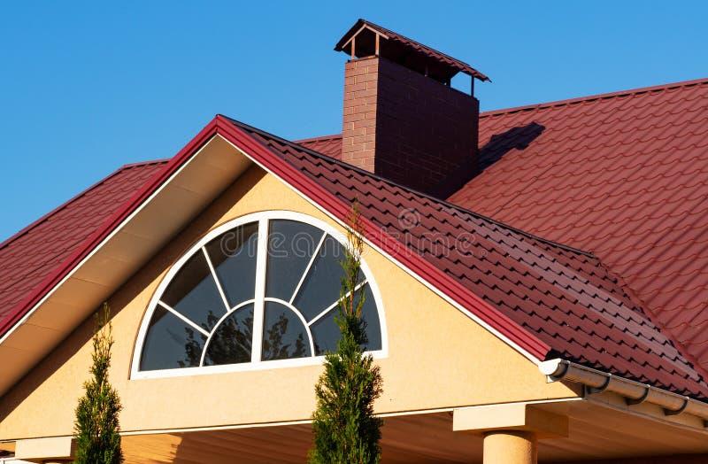 Het halve cirkelvenster en de baksteenschoorsteen op het rode metaal betegelen dak, huisbuitenkant stock foto's