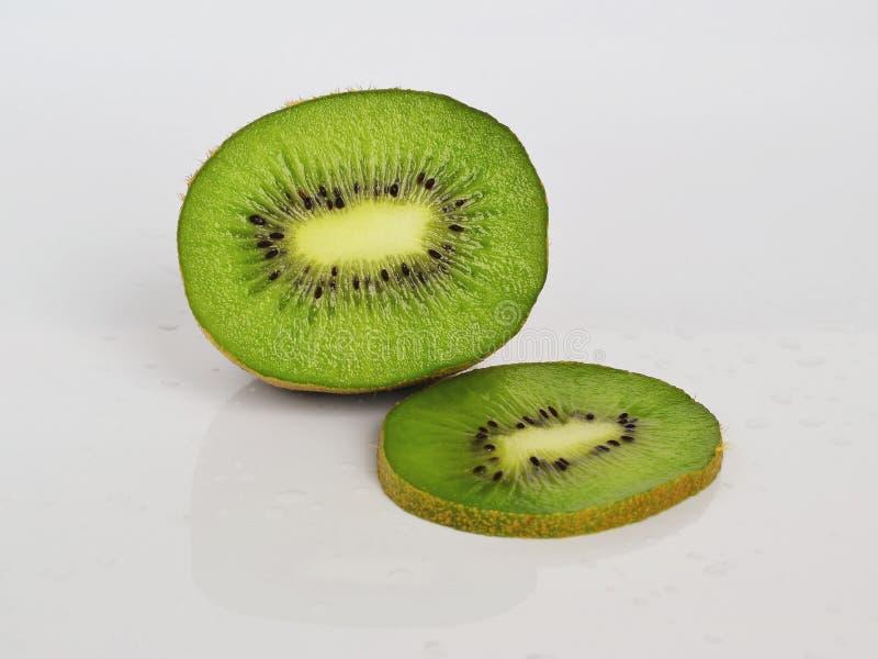 Het halve fruit en de groene plak van kiwi op een witte glanzende achtergrond met water dalen, gezond het eten concept royalty-vrije stock afbeeldingen