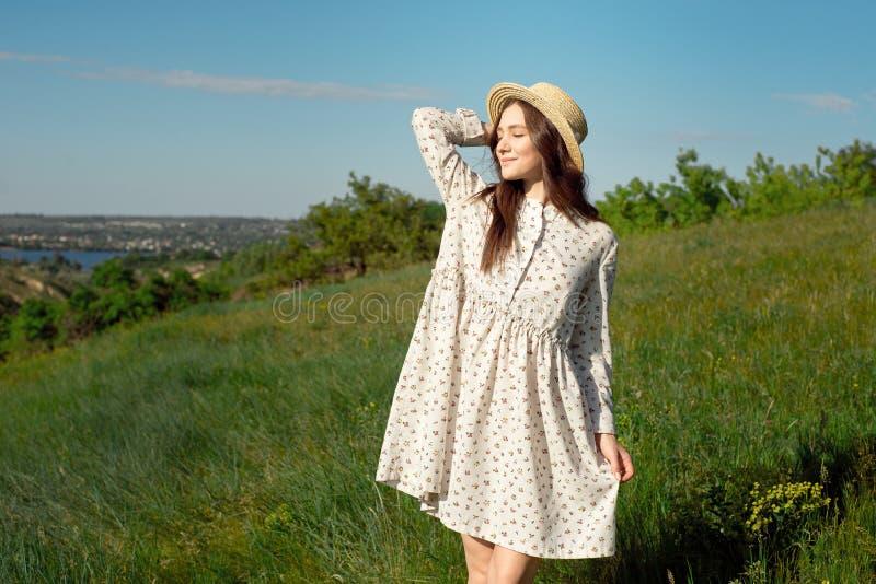 Het halve lengteportret van een charmante positieve vrouw kleedde zich in lange witte de zomerkleding met een strohoed van gelukk stock foto's
