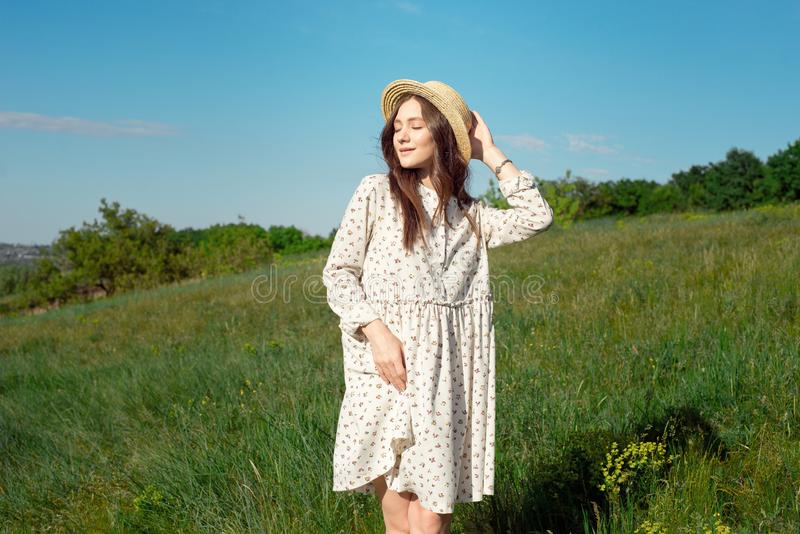 Het halve lengteportret van een charmante positieve vrouw kleedde zich in lange witte de zomerkleding met een strohoed van gelukk stock fotografie